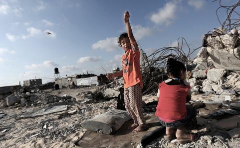 """ABS100. KHAN YOUNIS, FRANJA DE GAZA, 02/07/2015.- Dos niñas juegan junto a la casa destruida de su familia, afectada por el conflicto entre Israel y Palestina en 2014, en el barrio de Khoza-a en el este de Khan Younis, en la Franja de Gaza hoy, jueves 2 de julio de 2015. Cientos de palestinos se manifestaron hoy en el barrio de Shuafat, en el territorio palestino ocupado por Israel de Jerusalén Este, para pedir una Tercera Intifada, en el primer aniversario del asesinato del adolescente Mohamed Abú Jdeir. """"Queremos una nueva Intifada"""", gritaban los manifestantes, informó el medio digital Ynet. EFE/MOHAMMED SABER"""